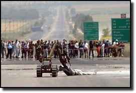 Israeli robot bomb removal machine drags badly wounded Palestinian suspected of possessing more explosives.
